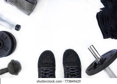 Top view of black tone fitness accessories on white background with copy space, equipment for weight training exercises concept