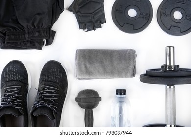 Top view of black tone fitness accessories on white background, equipment for weight training exercises concept