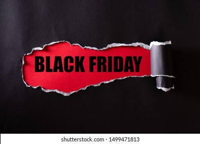 Top view of Black torn paper and the text black friday on a red background. Black Friday composition.