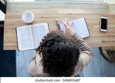 top view of black woman sits and makes notes while studying the bible