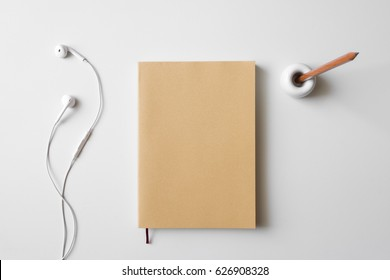 Top view blank book brown cover paper, earphone, and wood pencil in holder on white desk background