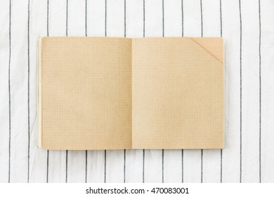 Top view of blank brown notebook on white and blue stripe pattern cloth texture background.
