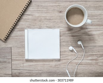 Top view of blank compact disc (CD) with cover, earphones, notebook and coffee on wooden background ( Space for picture and text )
