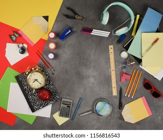 A top view blank copsypace area on a back to school chalkboard education background with various school supplies around to add your message.