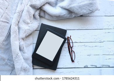 Top view of a blank ebook, a black notebook on a white rustic wood surface next to a fluffy throw blanket. Flataly of an ereader, notebook and blanket with copy space