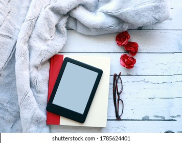 Top view of a blank ebook, a hardcover book on a white rustic wood surface next to a fluffy throw blanket. Flataly of an ereader, notebook and blanket with copy space