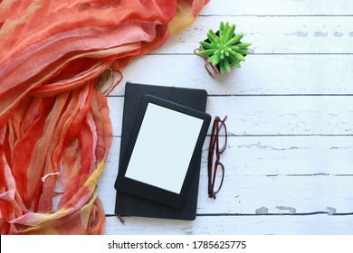 Top view of a blank ebook, on black notebook on a white rustic wood surface next to an orange scarf, reading glasses a succulent.  Flataly of an ereader, notebook with copy space