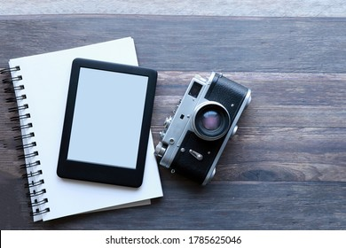 Top view of a blank ebook, a  sketchbook on a  rustic wood surface next to a  vintage camera . Flataly of an ereader, notebook and a vintage camera with copy space