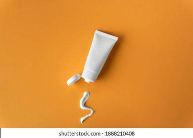 Top view blank label facial skincare white tube bottle with lid open product squeezed lotion or cream texture on plain solid orange background