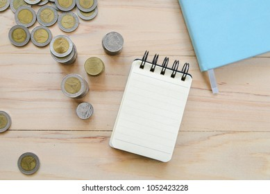 Top view of blank note book and Thai coins on wooden table - finance, business concept