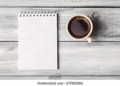 Top view of blank note pad and coffee cup on white wooden table