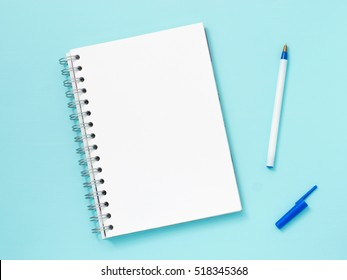 Top view of blank note paper with pen on blue wood table for background. Back to school and education concept