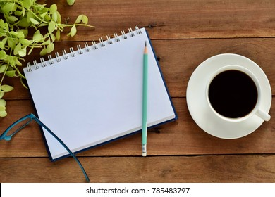 Top view of blank notebook and pencil next to cup of coffee on old wooden table .Vintage effect background.