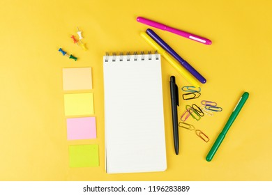 Top view of blank notebook and school supplies like colored mark