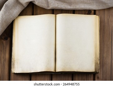 Top view of blank old book with vintage pages and sackcloth on wooden table