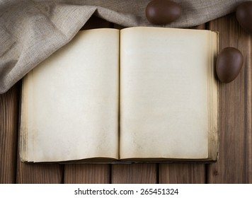 Top view of blank old book with vintage pages and chocolate eggs in the sackcloth on wooden background