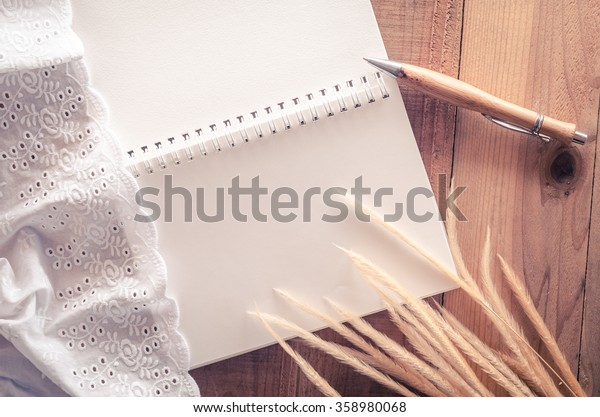 Top view of blank opened notebook page on a wooden table