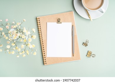 Top view blank paper Notebook, flowers, golden paper binder clips, cup of coffee and pen. Desktop mock up, Flat lay of green working table background with office equipment, mockup greeting card - Shutterstock ID 1907742037