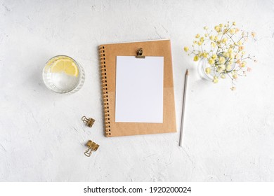 Top view blank paper Notebook, flowers, golden paper binder clips, water with lemon and pen. Desktop mock up, Flat lay of white working table background with office equipment, mockup greeting card