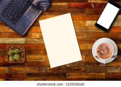 Top view of blank paper on wood office table with smartphone, laptop and hot coffee cup.