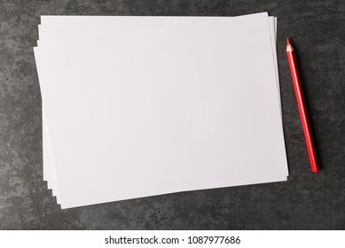 Top view of blank paper sheet and red pencil.