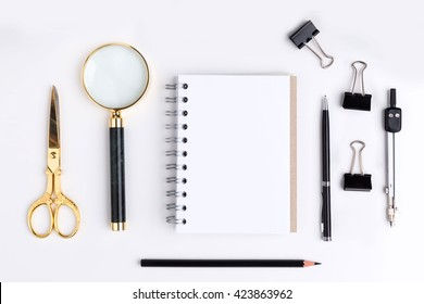 Top view of blank spiral notepad, golden scissors, magnifier and other stationery items on white background. Mock up