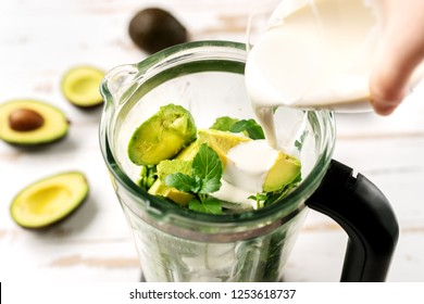 Top view of blender with avocado peaces