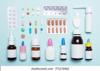 Top view blisters with tablets, spray for the throat, drops in the nose, syrup. Green background