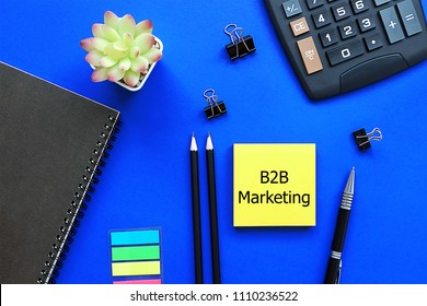 Top view blue background desktop with yellow Note write text B2B Marketing for business and finance concept.