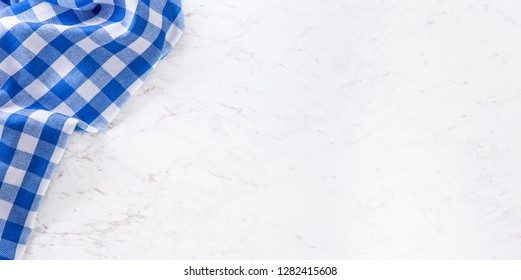 Top of view blue checkered tablecloth on white marble table.