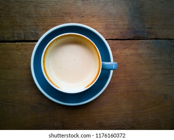 top view blue cup of coffee latte with sip mark on wood table background.