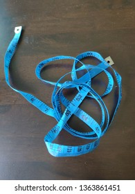 Top view of a blue measuring tape on the dark table.