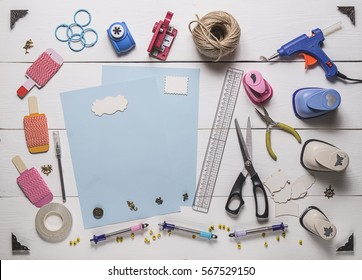 top view of blue pages and layout tools for needlework and scrapbooking on wooden boards with copy space