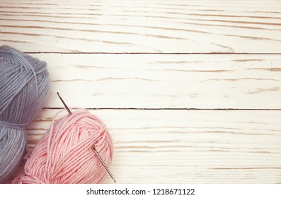 top view of blue and pink wool balls of thread and crochet hook on white wooden knitting background.