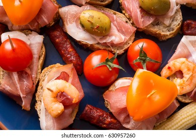 Top view of blue plate with variety of mediterranean appetizers - tapas