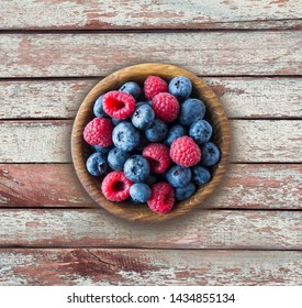 Top view. Blue and red berries in bowl. Ripe raspberries and blueberries on a wooden background.Background of mix berries with copy space for text. Mix berries on rustic background. Various fresh summ