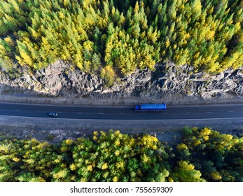 Top view at blue semi-trailer truck driving between rock tunnel in autumn green and yellow forests of Karelia, Russia