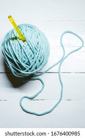Top view of blue yarn ball with woolen thread on white wooden background