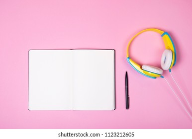 Top view of blue and yellow headphones, opened notebook and pen on pink background. Flat lay. Copy space.