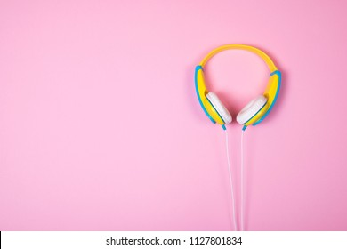 Top view of blue and yellow headphones on pink background. Flat lay. Copy space.