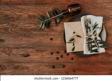 Top view Boho wedding dinner reception table set up. Top view, olive branches on  wooden background