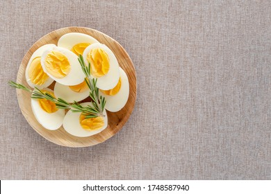 Top view of boiled eggs in wooden bowl on cotton fabric background with copy space. Boiled egg diet.