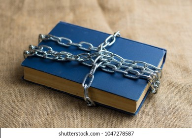 top view of a book in a blue cover lying on burlap, the book is wrapped in a chain, a forbidden