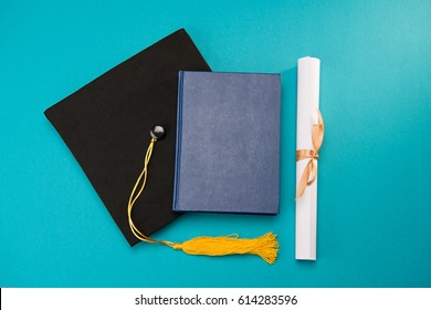 Top view of book, graduation mortarboard and diploma isolated on blue, education concept