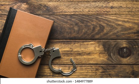 Top view book and handcuffs on wooden table