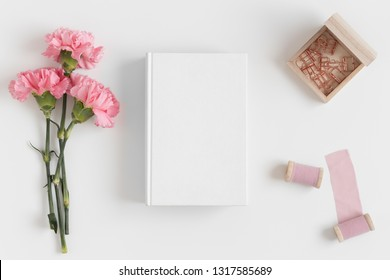 Top view of a book mockup with a bouquet of pink carnations and workspace accessories on a white table.