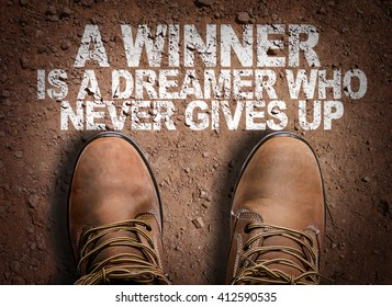 Top View of Boot on the trail with the text: A Winner is a Dreamer Who Never Gives Up