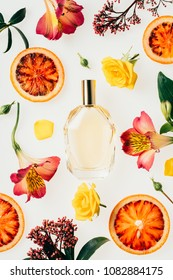 top view of bottle of aromatic perfume surrounded with flowers and blood orange slices on white