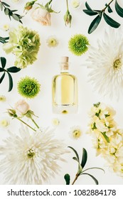 top view of bottle of aromatic perfume surrounded with flowers and green branches on white