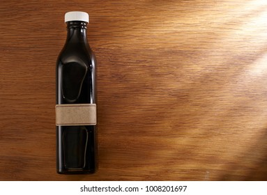 top view of bottle of the black vinegar on wooden background